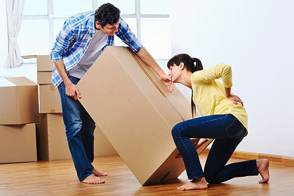 image of a man holding a box and a woman holding her back